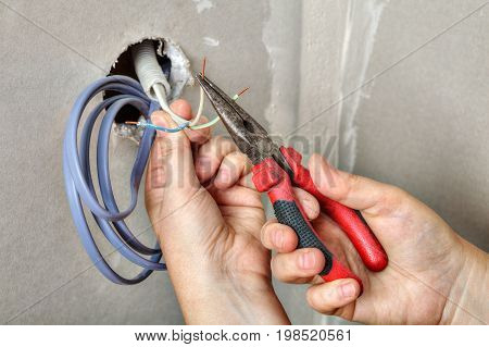 The electrician's hands stretch the wiring through the hole in the wall of the plasterboard strip cables before pulling them.