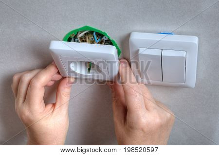 Fixing electrical wall outlet and light switch electrician fitter hands close-up.