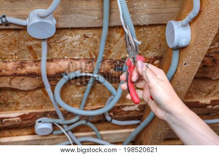An electrician hand with pliers during installation mount light junction box wiring for ceiling.