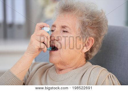 Elderly woman using inhaler during asthmatic attack at home
