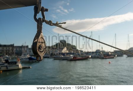 Early morning sun illuminates pulley or winch in front of the harbor at Ilfracombe, Devon