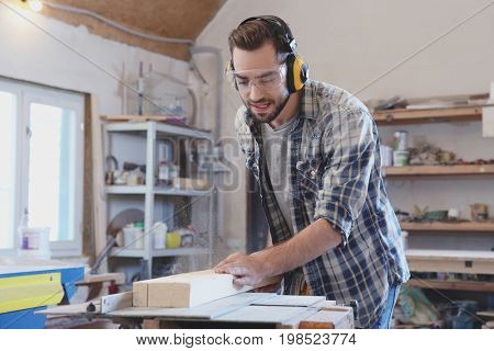 Young carpenter working with circular saw in shop
