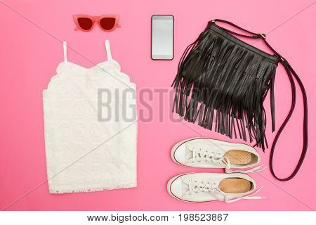 White Lace Top, Black Handbag, White Sneakers, Glasses And Phone. Bright Pink Background. Fashionabl