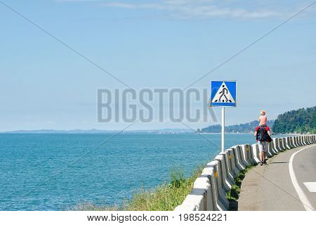 Man with his son on their shoulders walks along the highway against the background of the sea. Pedestrian crossing sign