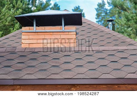 Modern roofing and decoration of chimneys. Flexible bitumen or slate shingles. The absence of corrosion and condensation due to the flexible roof