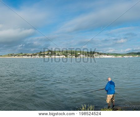 Male angler fishing from the coast in the sea at Appledore in North Devon, UK
