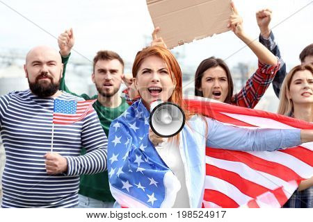 Group of protesting young people with American flag on street
