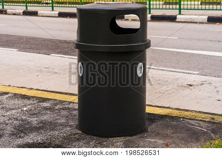 Black dustbin or trashcan beside the road Container beside country street