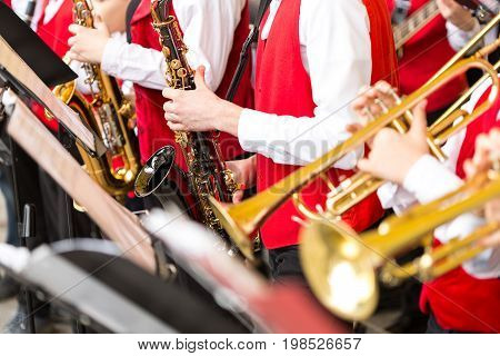 jazz band music performance concept - orchestra of wind instruments during the concert, selective focus on hands of musicians playing on trumpets and saxophones, closeup male in red costumes