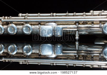 symphonic music concept - closeup on western concert flute lies on the pure black mirror surface, middle body section of instrument with majority of keys, marching, orchestra concerts, macro