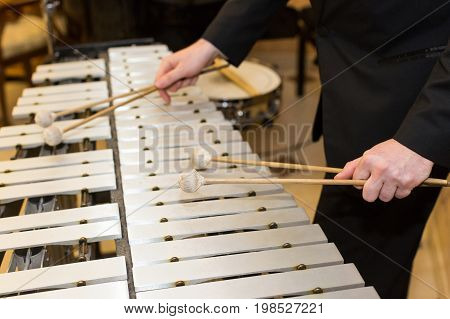 xylophone, percussion instrument concept - closeup on wooden bars with four mallets in human hands, performer in black dress, glockenspiel, orchestra concert, art of music, selective focus