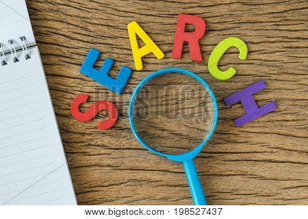 SEO Search engine optimisation concept as colorful alphabet SEARCH with magnifying glass and note paper on the wooden table.
