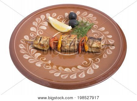 Sturgeon shish kebab with vegetables on a clay plate. Isolated on a white background.