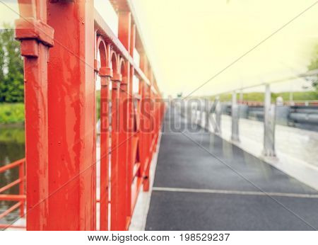 A Background With A Perspective View At The Red Fence And Blurred Asphalt Sideway