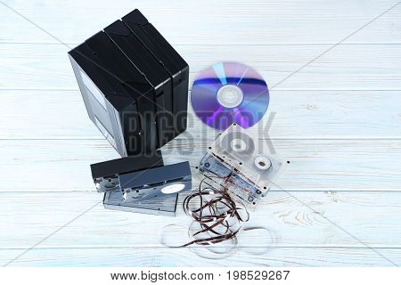 Video and music cassette tapes with CD disk on wooden table
