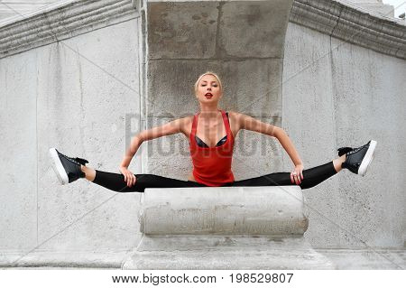 Gorgeous young blonde woman doing splits outdoors in the city street confidence femininity beauty sexy hot seductive flexible flexibility balance athletics fitness concept.