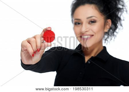 Studio shot of a beautiful young woman smiling happily holding out red casino token to the camera isolated on white copyspace.