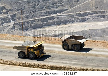 Two monster dump trucks pass each other in an open pit mine.