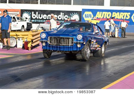CHANDLER, AZ - OCTOBER 2: A hot rod car pops a wheelie at the start of the race at the NHRA Pacific Division drag racing championship on October 2, 2009 in Chandler, Arizona.
