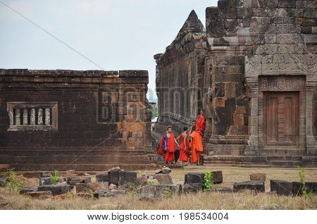 Laotian Monk And Novice Visit With Pray Buddha And God Statue At Vat Phou Or Wat Phu