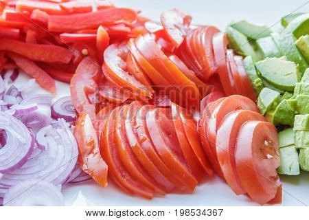delicious piles of freshly sliced avacado tomato and onion on serving plate