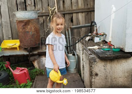 Little four-year-old dirty-faced girl with a yellow plastic watering-can on a Russian rustic background.