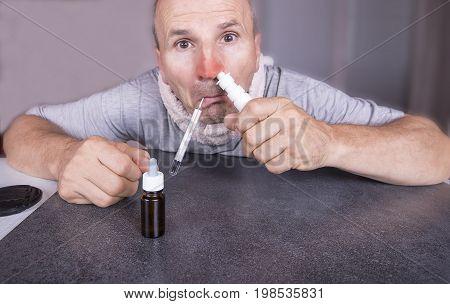Sick man with flu taking his nasal spray medicine