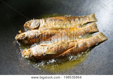 Fried fish. Three fishes frying in hot oil in pan or skillet.