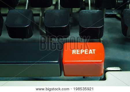 Red repeat button on typewriter. Do something again.