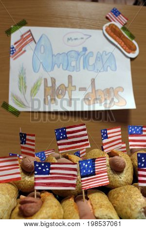 American hot dogs with small American flags close plan, bun and sausage and an inscription american hot
