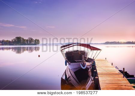 Boats moored to a wooden bridge. Poland Europe.