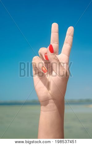 Counting woman hand. Hand gesture with sea on background.
