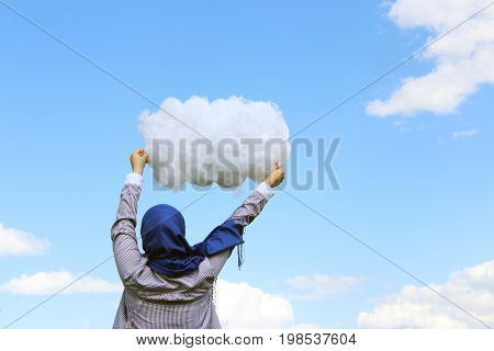 Muslim girl holding a cloud of cotton wool against the background of a summer