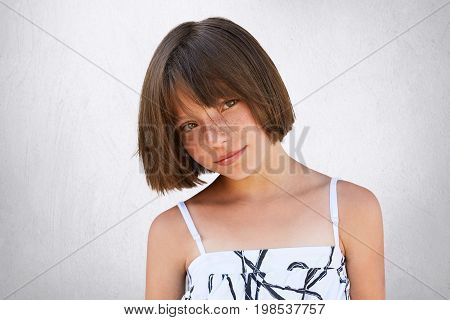 Pretty Little Girl With Freckles, Dark Eyes And Short Hairstyle Wearing Summer White Dress Posing Ag