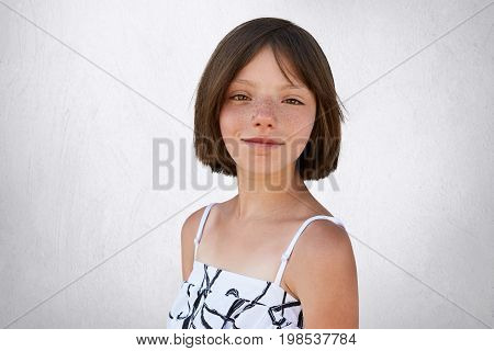 Portrait Of Freckled Little Girl With Dark Short Hair, Hazel Eyes And Thin Lips Wearing Black And Wh