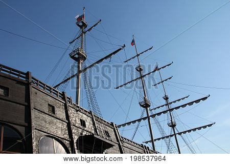 Masts Of An Old Sailing Ship On Blue Sky Background
