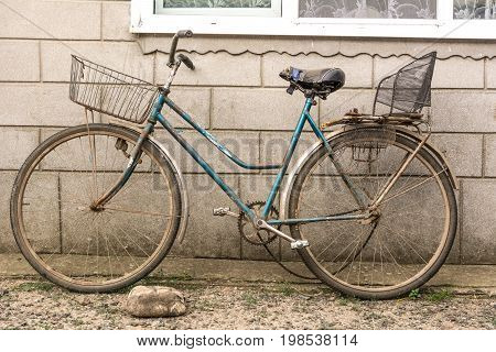 Old bicycle with a makeshift basket and a makeshift seat for the passenger on the trunk
