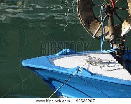 Prow of a wooden fishing boat with trawl winch on the deck . The fishing boat is moored in the harbor . Tuscany Italy
