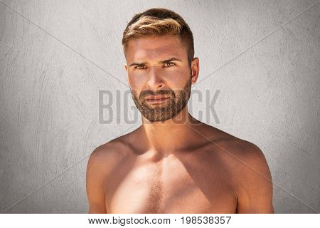 Horizontal Portrait Of Handsome Unshaven Man With Dark Eyes, Stylish Hairdo Staanding Topless Over G