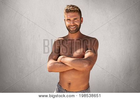 Waist Up Portrait Of Muscular Attractive Man With Trendy Hairstyle And Bristle, Keeping His Hands Cr