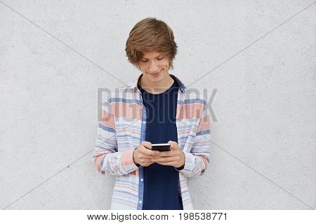 Fashionable Teenage Boy Wearing Shirt, Holding Cell Phone In Hands, Messaging With Friends Or Playin