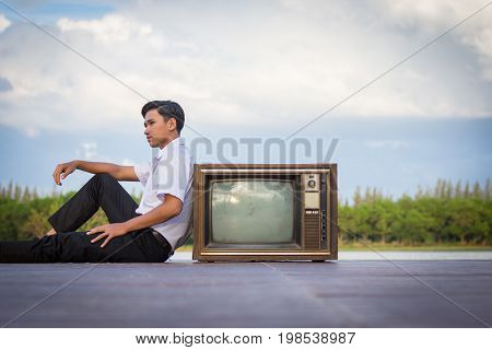Man Sitting On A Pier With Old Televisions.