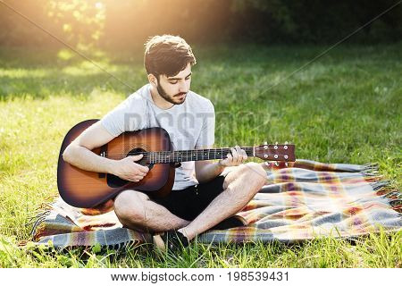 Portrait Of Attractive Stylish Bearded Guy With Guitar Sitting Crossed Legs On Green Grass, Playing