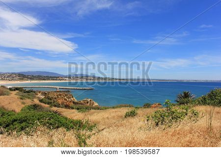 Beautiful landscape overlooking Atlantic ocean coast in South Portugal. Summer nature panoramic scene: hills, water, beach and clear blue sky background. Photo of long distance outdoor sunny day view
