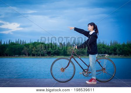 A Young Woman Riding A Bike And Pointing To The Sky At Sunset.