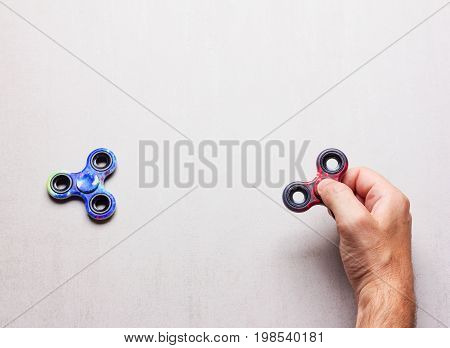 popular toys hand spinner in male hand on gray background with space for text. mock up for text phrases lettering
