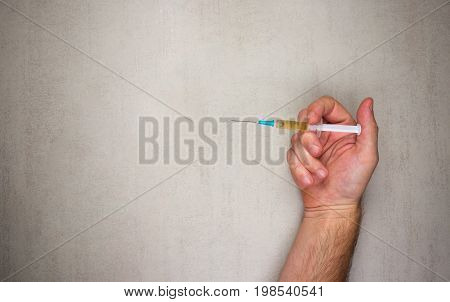 Male hand with disposable syringe for injection on a gray background. mock up for text phrases lettering