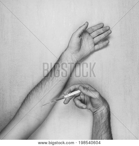 hands of man making himself an injection of disposable medical syringe on a gray background top view closeup. black and white photo