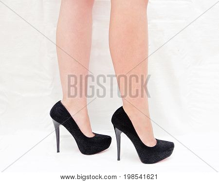 Female legs in black high-heeled shoes isolated on white background.