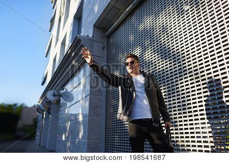 People and modern lifestyle concept. Urban portrait of attractive young male in stylish sunglasses and leather jacket standing outdoors with hand raised hailing a taxi going on date or meeting